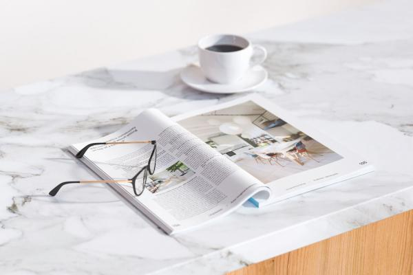 open magazine, glasses and  cup of coffe